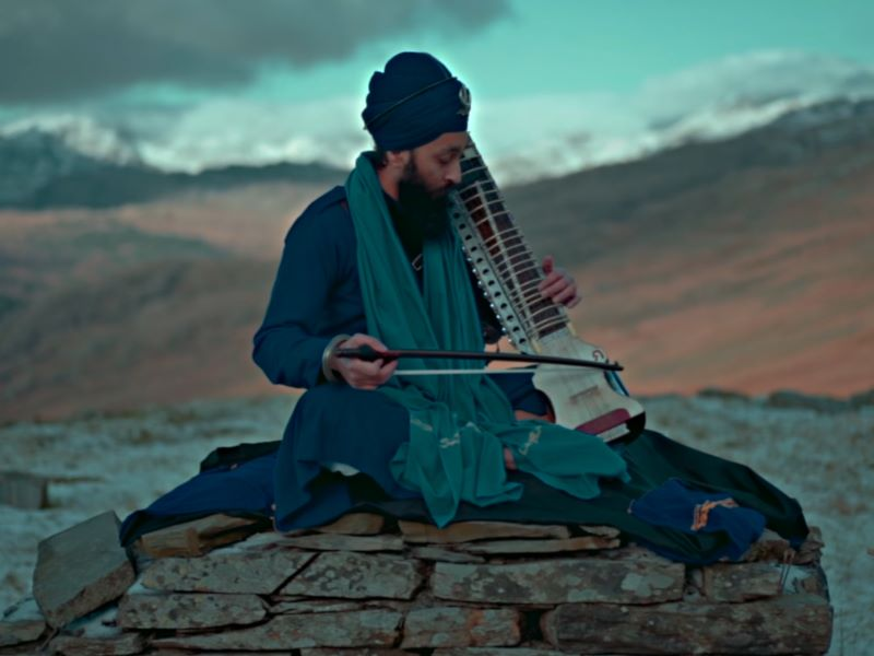 Nihang Singh sitting atop a mountain playing a string instrument