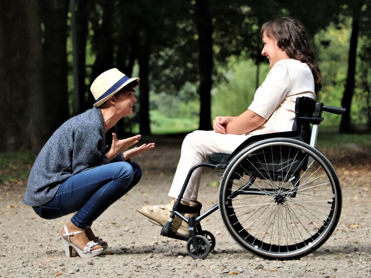 Two people laughing together, one of whom is wheelchair bound